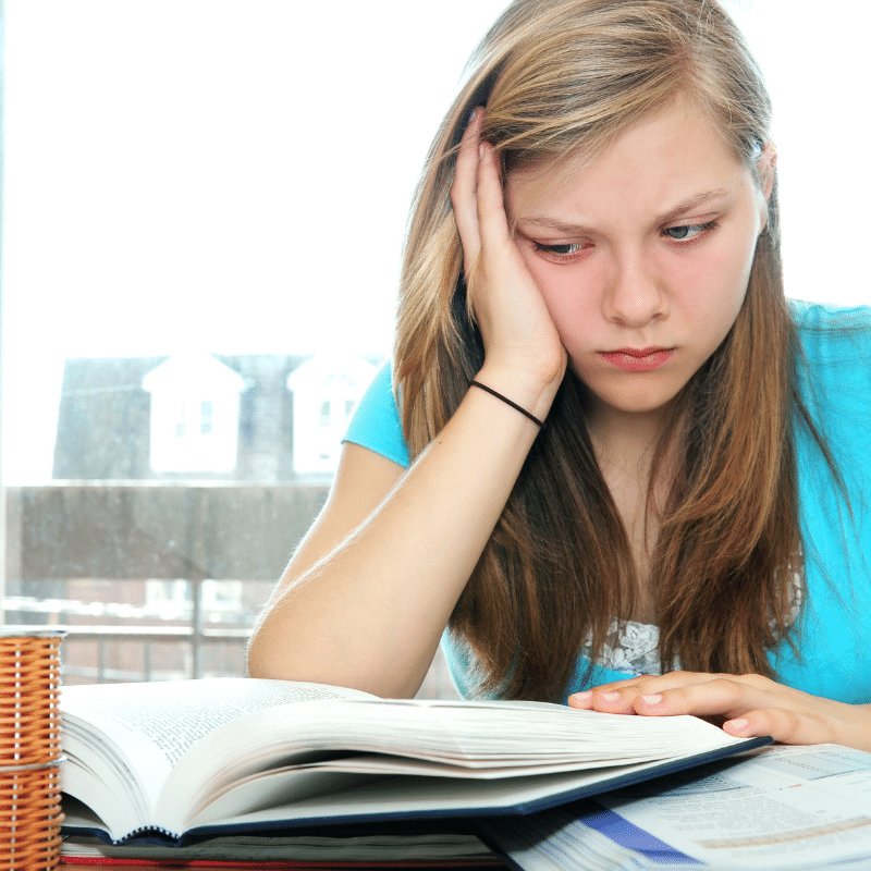 A female student experience test taking anxiety. She is looking at an open textbook. Her face rests in the palm of her right hand, and her face displays anxiety and frustration.