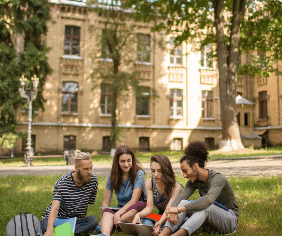Four students discuss a topic outside a college building, seated on a grassy area.